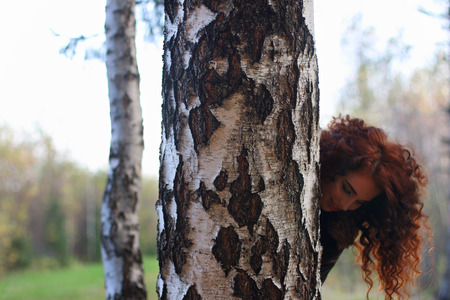 'hide out': Pretty smiling woman looks out of big birch in autumn forest, shallow dof