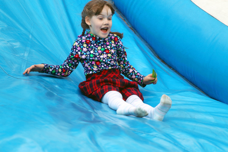 Happy little cute girl rides on inflatable slide outdoor in park Standard-Bild