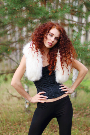 Pretty woman in corset with white fur and curly hair poses in pine forest