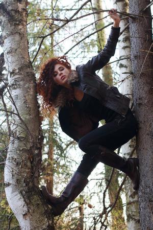 포리스트의 오래 된 전나무 나무에 곱슬 머리 포즈와 예쁜 여자 부츠