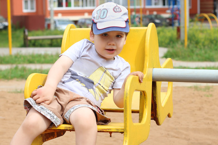 playground rides: Little cute happy boy rides on carousel on playground at summer day