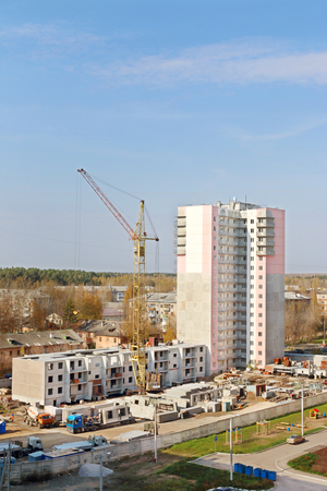 Crane on construction site and part of new tall concrete building at autumn day  Stock Photo
