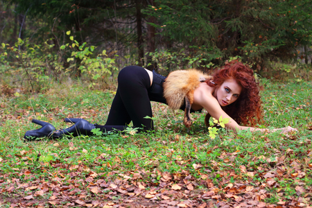 face in tree bark: Beautiful girl with curly hair poses on grass as animal in autumn forest Stock Photo