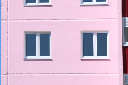 prefab: Part of pink residential building with windows with double glazing at sunny day
