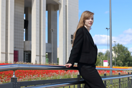 Pretty young woman in black suit poses near railing in sunny town Stock Photo