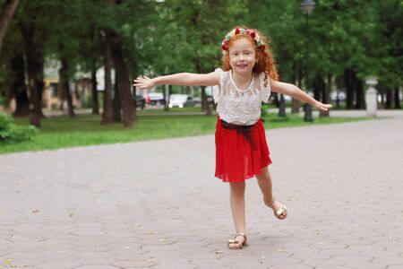 Little smiling girl with red hair depicts bird in green summer park, shallow dof