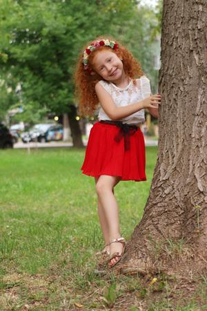 Little cute girl poses near big tree in summer park, shallow dof