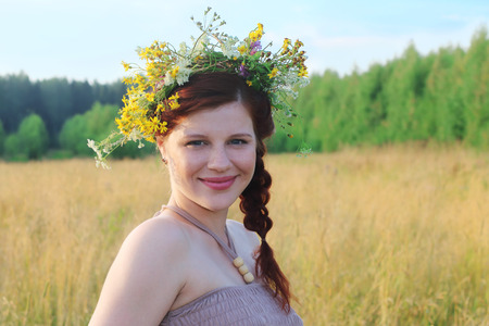 Pretty young woman in wreath poses among dry grass at summer day