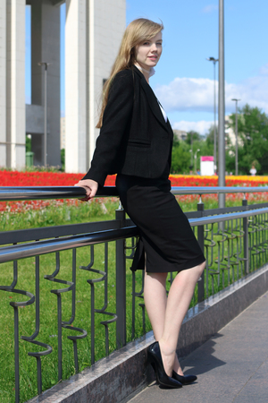 Beautiful woman in black suit poses near railing in sunny town