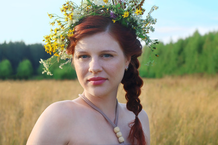 salud sexual: Beautiful freckled woman in wreath in dry field at summer day