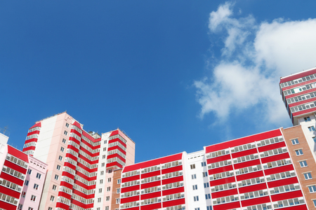 Part of residential building with balconies at sunny day, clouds, under view Stock Photo