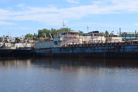 pleasure craft: Big rusty cargo ships are in bay on river at summer sunny day