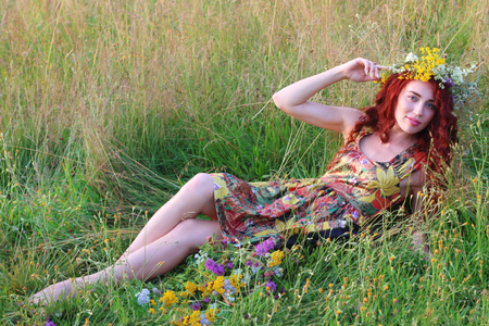 Beautiful woman in wreath with red hair lies in field at summer day
