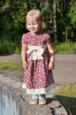 Little pretty blonde girl in dress stands in park at sunny day and smiles