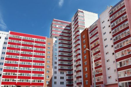 prefab: Part of pink residential building with many red loggias at summer day Stock Photo