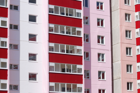prefab: Part of new pink residential building with red balconies and double glazing at sunny day