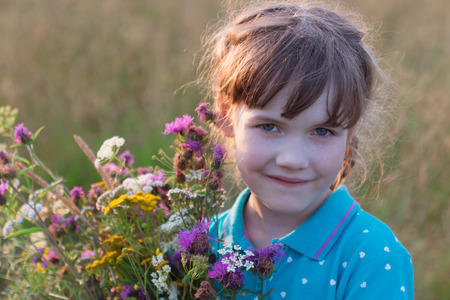 Little girl holds wild flowers and smiles in dry field at summer day Stock Photo