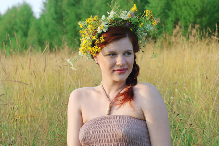 Beautiful freckled woman in wreath of wild flowers in dry field at summer day