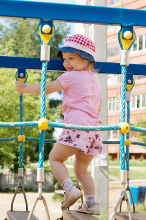 jungle gyms: Little cute girl in hat climbs on children playground at sunny day