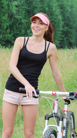 Beautiful sporty girl in shirt and shorts decided to ride a bike outdoors on a Sunny day