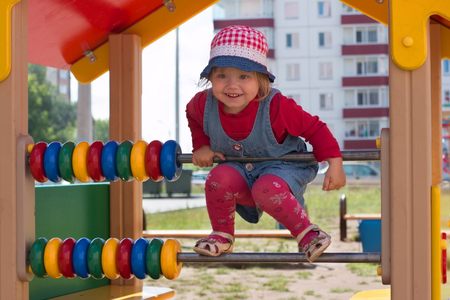 Little pretty girl in hat climbs on children playground at sunny day