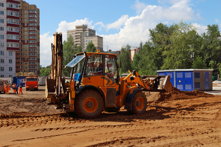 Yellow tractor works on construction site at summer sunny day