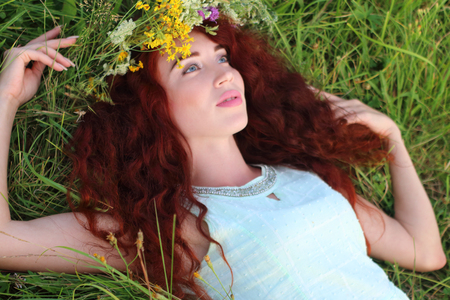 Woman in wreath lies on green grass and looks up on meadow at summer day Stock Photo