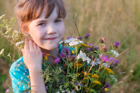 Happy little girl holds wild flowers and smiles in dry field at summer day
