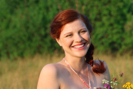 Beautiful freckled woman laughs at sunny day outdoor at summer