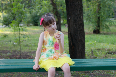 healty: Beautiful little girl in color dress sitting on bench with ice cream in hand