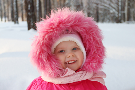 Little cute girl in pink stands in forest and smiles in winter sunny day Stock Photo