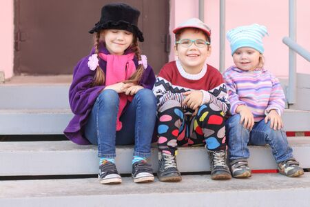 entryway: Three little children in bright clothes sitting on the stairs at the entrance