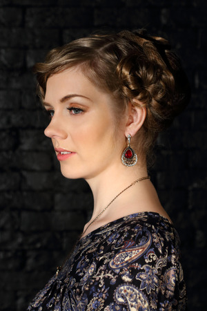 updo: Pretty young woman with makeup and hairdo poses in dark studio