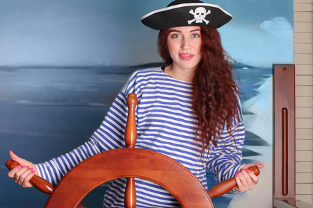 seaway: Dark-haired girl with a beautiful smile in a vest and a pirate hat holding the steering wheel