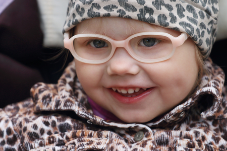 Happy little cute girl in fake glasses and leopard print dress smiles Stock Photo