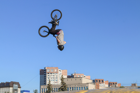 Young man makes a revolution in air on bike during the event jump aeromat in the Perm Region