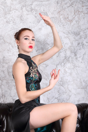 Beautiful woman with makeup as geisha poses on black leather sofa in studio