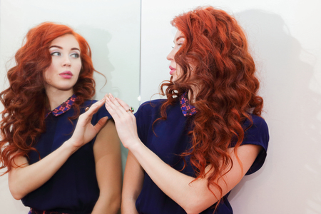 specular: Young woman with beautiful curly hair standing at the mirror and looks at her reflection