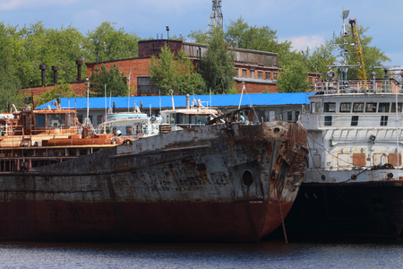 River bay with rusty cargo ships on sunny day, ships bow with anchor Stock Photo