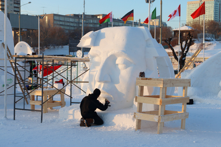 PERM, RUSSIA - JAN 18, 2017: Artist makes sculpture Big face in Ice town, Perm Ice Town 2017 Ekosad - largest in Russia