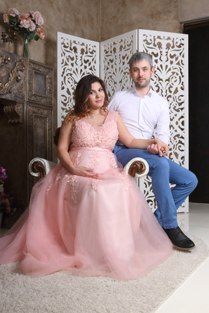 Man and pregnant woman in pink pose on baroque armchair in studio Stock Photo