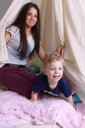 Mother and her little cute son play in wigwam with pillows at home, focus on kid