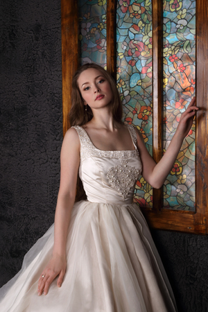 Beautiful woman in long dress poses near window in black studio