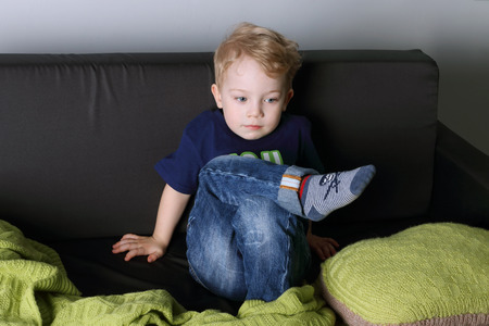 Cute little boy sits and thinks on black couch with green plaid in room
