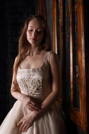 Pretty young woman in long dress dreams near window in black studio