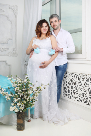 healthy body: Pregnant woman in dress and man with baby bootees in bedroom Stock Photo