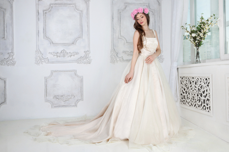 Beautiful woman in pink roses wreath and in long dress poses in white studio