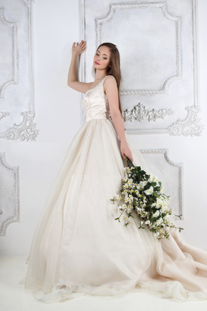 Young woman in long dress holds white flowers in white studio near wall Standard-Bild