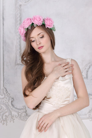 Beautiful woman in roses wreath with long hair poses in white studio