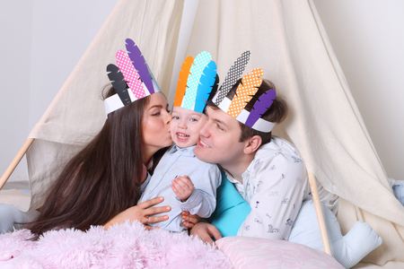 Father, mother, little son pose in wigwam with indian feathers in studio, woman kisses boy Stock Photo